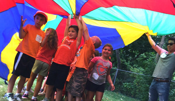 children playing under rainbow colored tarp