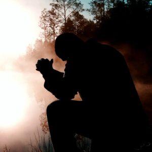man kneeling next to lake